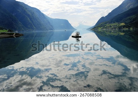 The reflection of the cloudy sky is seen in the Lustrafjord in Norway. - stock photo