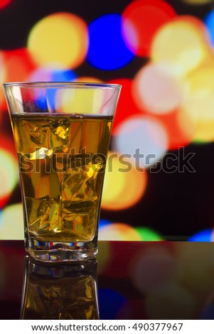 the refreshing juice with ice on a bright multi-colored background
