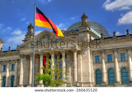 The Reichstag building in Berlin. Flag of the Federal Republic of Germany is waving in front of the national german parliament. - stock photo
