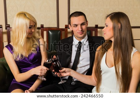 The relationship between man and woman. The concept of a love triangle. Human emotions - jealousy, betrayal, jealousy, love. Two beautiful girls and a guy on a green leather couch. - stock photo
