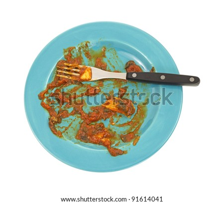 The remains of a plate of ravioli with fork on a blue plate.