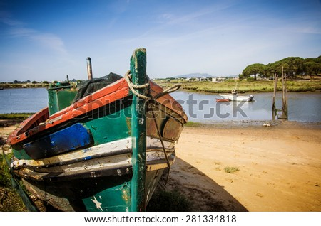 The remains of an old fishing boat rotting on the river shore - stock photo