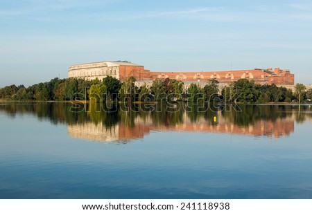 The remains of the large Congress Hall or Kongresshalle at the Nazi Parade grounds and reflected in still lake in Nuremberg, Germany - stock photo