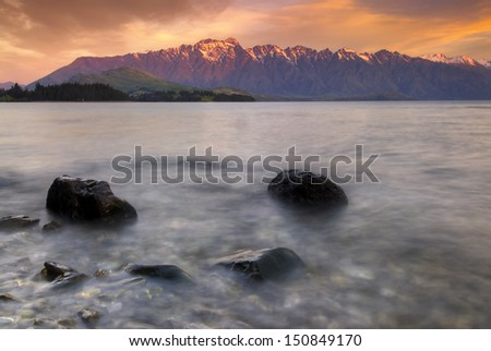 The Remarkables mountain range lit up at sunset over Lake Wakatipu, Queenstown, South Island, New Zealand. - stock photo