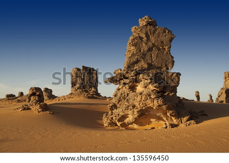The removed rocks the remains of ancient volcanoes in the middle of the Libyan Desert. Dense sand with edge structure. Southern Libya. - stock photo