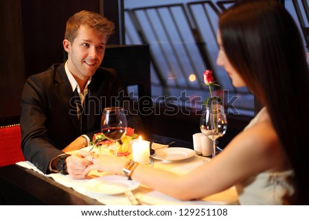 The restaurant guy holding a beautiful Brunette by the hand - stock photo