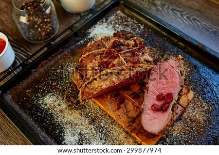 The restaurant serves an unusual meat directly on the baking sheet, designed for a big company, sauce can be different but perfect dish for the sauce from the berries with the addition of hot peppers - stock photo