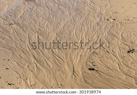 The retreating tide leaves a delicate pattern on the wet sandy shore at Ocean Beach Bunbury, Western Australia  on a sunny morning in late  winter. - stock photo