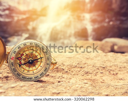 The retro compass on the rock with waterfall blurred background and sunlight. Vintage style and filtered process - stock photo