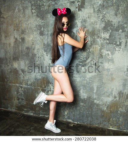 The retro photo of a cute pin-up girl in sunglasses with vintage and mouse ears.Summer mood,urban background,fashion look.Portrait of dancing girl on party.Party girl,Posing in mouse ears,hipster  - stock photo