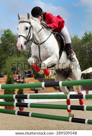 The rider on the white racehorse overcome high obstacles in the arena for show jumping on background blue sky - stock photo