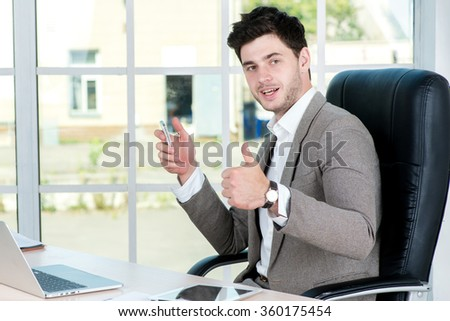 The right decision. Successful confident businessman sitting in office at the table and working on a laptop while raising his arms up and cheers. Young businessman