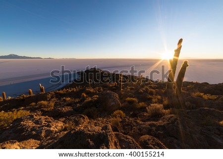 The rising sun at the horizon over the majestic Uyuni Salt Flat, among the most important travel destination in Bolivia. Wide angle shot in backlight from the Incahuasi Island with glowing cactus. - stock photo