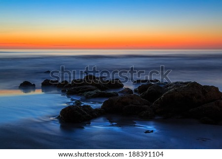 The rising sun paints the sky over a Florida beach south of St. Augustine with naturally occurring coquina stone. - stock photo