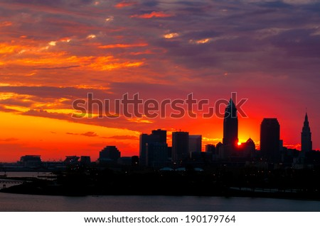 The rising sun peeks out from behind nearly silhouetted buildings of downtown Cleveland Ohio - stock photo