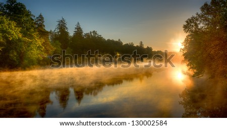the rising sun shining on a misty lake with forest in background