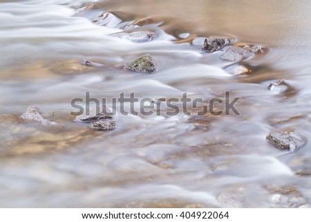 The river flows through the stones. The water flow crosses the barrier from the stones. - stock photo