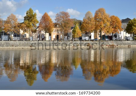 The river Mayenne at Laval with fall foliage trees, commune in the Mayenne department in north-western France