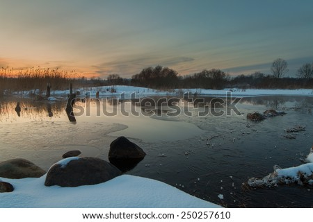 the river with the destroyed bridge at sunset in the winter