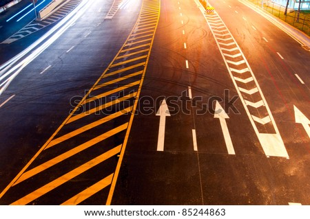 The road at night, under lights and into the orange. - stock photo