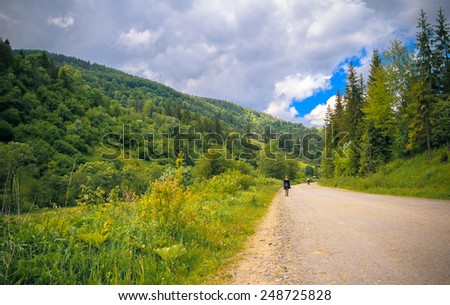 The road between the blue mountains in the Carpathians and stretching into the distance girl and man - stock photo