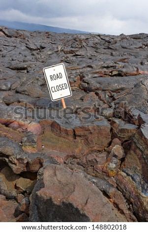 The Road Closed sign on the road buried in lava  from the eruption of Kilauea, Big Island Hawaii.  selective focus