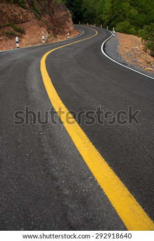 The road curved empty