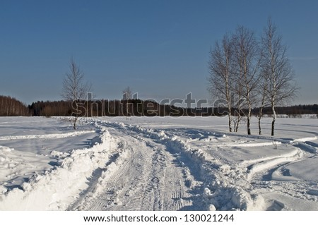 The road in snow on forest background, winter sunny day - stock photo