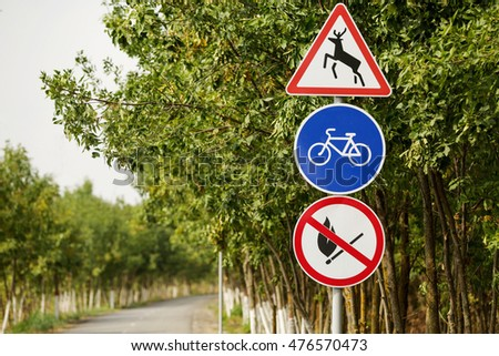 The road in the forest. Road signs. Sign allowed to ride the bike. The sign is forbidden to make a fire in the forest. Sign of wild animals, deer.