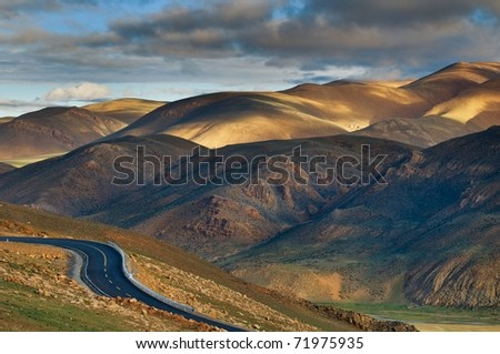 The road in Tibet plateau at sunset. - stock photo