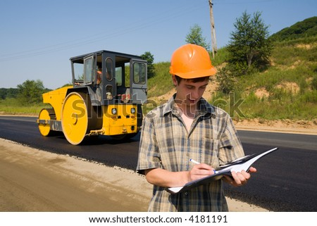 The road inspector on a working platform. Stacking of new asphalt. - stock photo