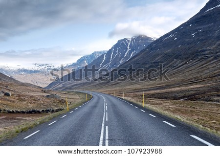 The road leading through the valley between the mountains - stock photo