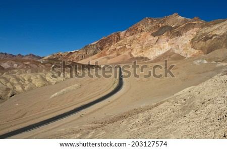 The road leading to the Artists Palette in Death Valley, California. Various mineral pigments have colored the volcanic deposits found here. - stock photo