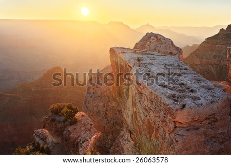 The rocks of the Grand Canyon (South Rim) at sunrise with the sun just above the horizon.