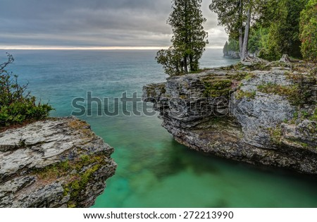 The rocky coast of Door County, Wisconsin's Cave Point displays beautiful colors in the light of a stormy sunrise. - stock photo
