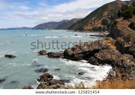 The rocky coast of Kaikoura looking south towards Christchurch. A popular seal colony and whale watching tourist destination on the east coast of the South Island in New Zealand. - stock photo
