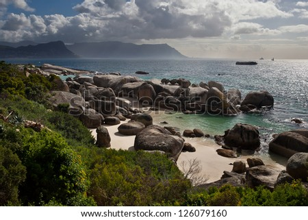 The rocky coastline of False Bay near Table Mountain National Park in South Africa is pleasing.  The bay is massive and known for its Great White shark population. - stock photo