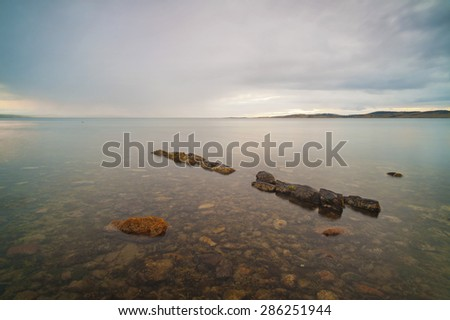 The rocky ocean floor can be seen through the very clear water, broken only by a small line of rocks pointing to the horizon. - stock photo