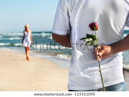 the romantic date concept - man with rose waiting his woman on the sea beach at summer - stock photo