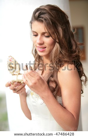 the romantic portrait of the brides in white-golden gown with gift in hand - stock photo