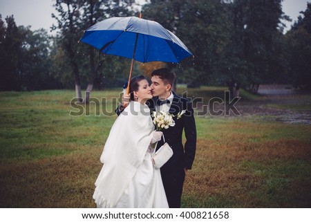The romantic walking of newlyweds. The groom and bride are walking under umbrella in the rain in the park. The groom is kissing a bride. Bride is smiling with pleasure. Tis is their wedding day. - stock photo