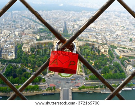 The romantically love inscribed padlocks on the Eiffel Tower, Paris France. In the background panorama of Paris.  - stock photo