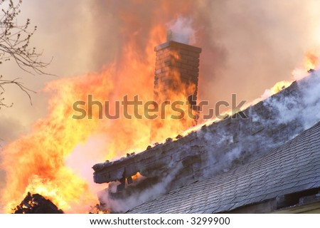 The roof and chimney of a house on fire - stock photo