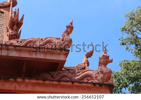 The roof of a Buddhist temple of the snake in Thailand on Koh Samui on the background of blue sky