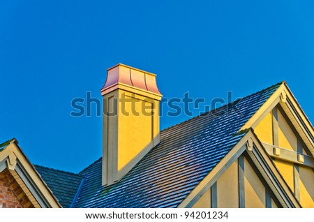 the roof of the house with nice chimney under the blue sky - stock photo