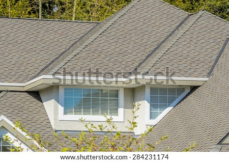 The roof of the house with nice window and white frame. - stock photo