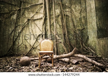 the roots on the wall and the empty chair - grunge and textured - stock photo