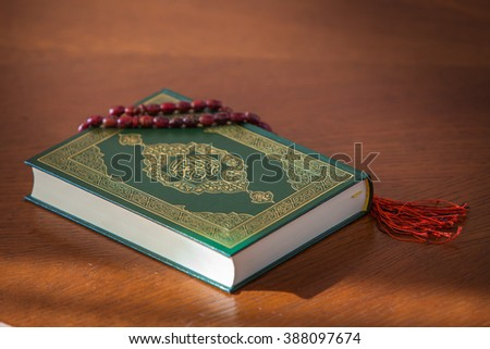 the rosary and the holy book the Koran. On the cover of the book in Arabic is written the name of the book (translated ) - Quran . - stock photo