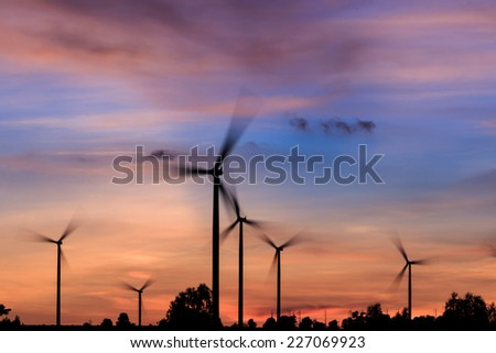 The rotation of the wind turbines silhouette at sunset