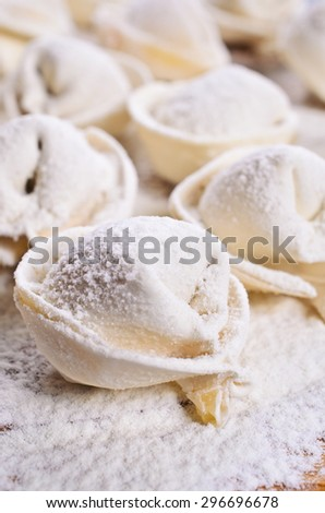 The round shaped dumplings, sprinkled with flour on wooden surface - stock photo